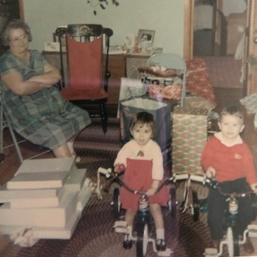 Grandma looking on as cousin Steve and I try out our new tricylces--1966
